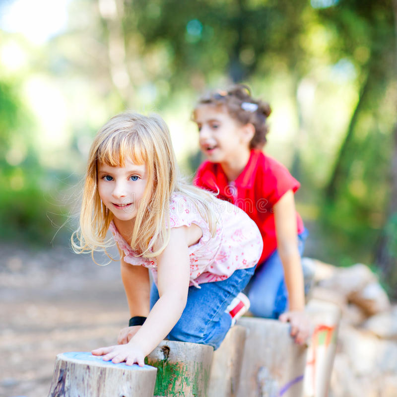 Kid girls playing on trunks in forest nature royalty free stock photos