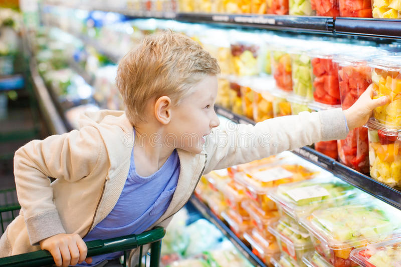 Kid at grocery store. Positive 6-year old boy buying healthy fruits at supermarket or grocery store helping his parents stock photo