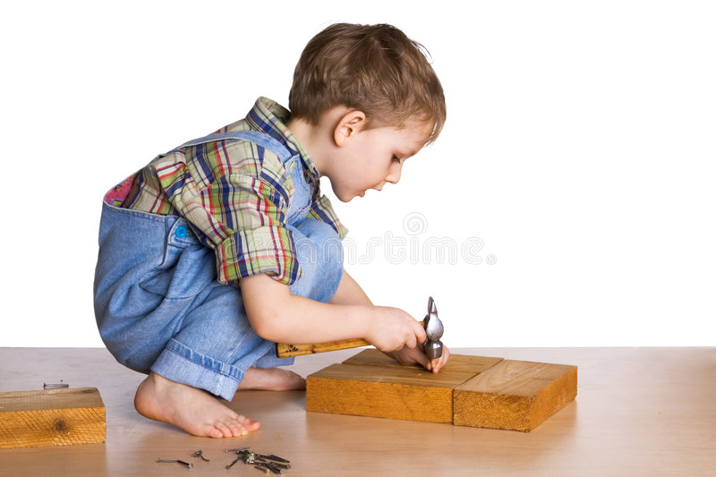 Kid hammers a hammer in nails royalty free stock photos