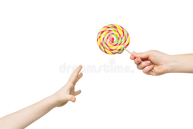 Kid hand reaching for big colorful lollipop. Kid reaching for big colorful lollipop in mothers hand, isolated on white background royalty free stock image