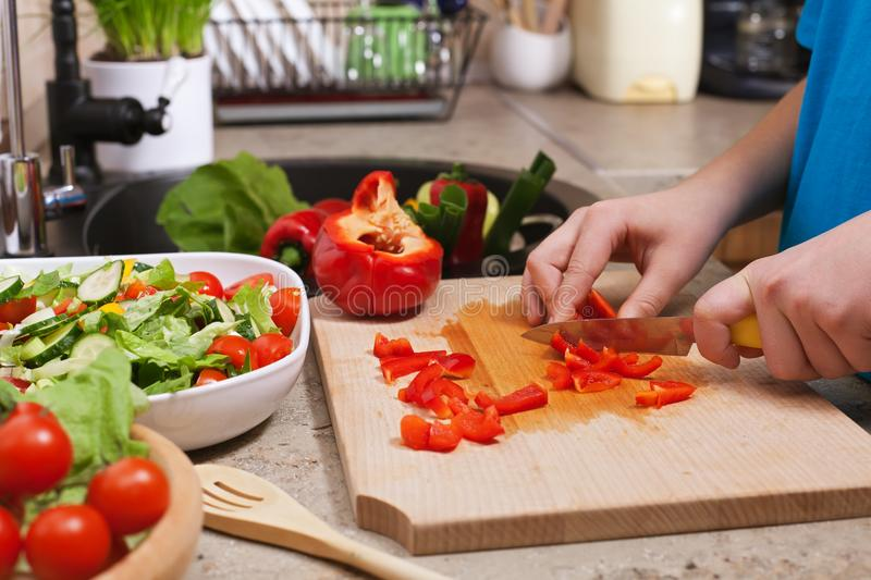 Kid hands chopping red bellpepper for a delicious vegetable salad. Closeup on cutting board in the kitchen, shallow depth royalty free stock photos