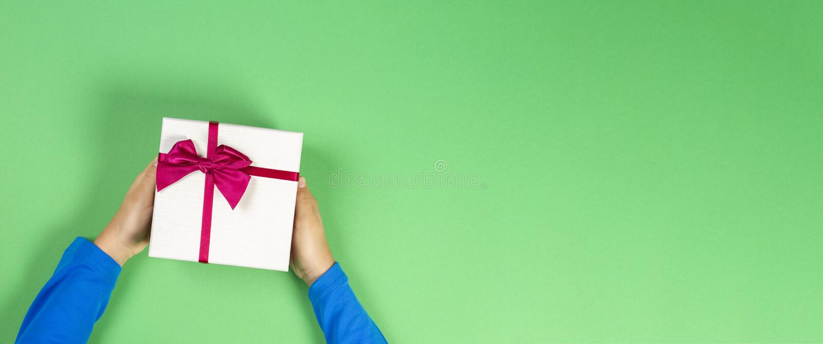 Kid hands give wrapped present box with ribbon over green table, top view.  royalty free stock images
