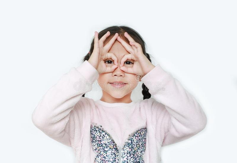 Kid with hands glasses in front of her eyes isolated on white background. Little asian girl looking through imaginary binocular stock photo