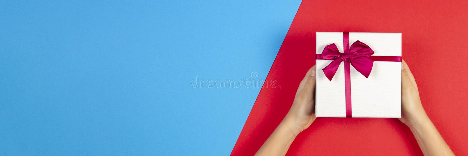 Kid hands holding present gift box with ribbon on red and blue background royalty free stock images