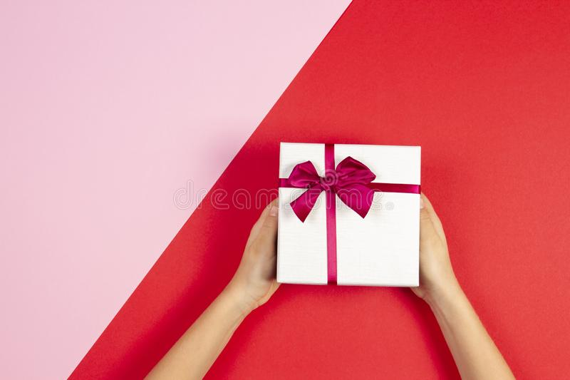 Kid hands holding present gift box with ribbon on red and pink background. Congratulations with Christmas, mother`s day royalty free stock photos
