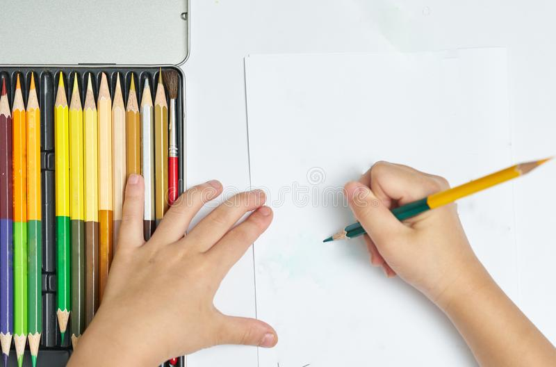 Kid Hands holds color pencil and think about drawing things on w royalty free stock images