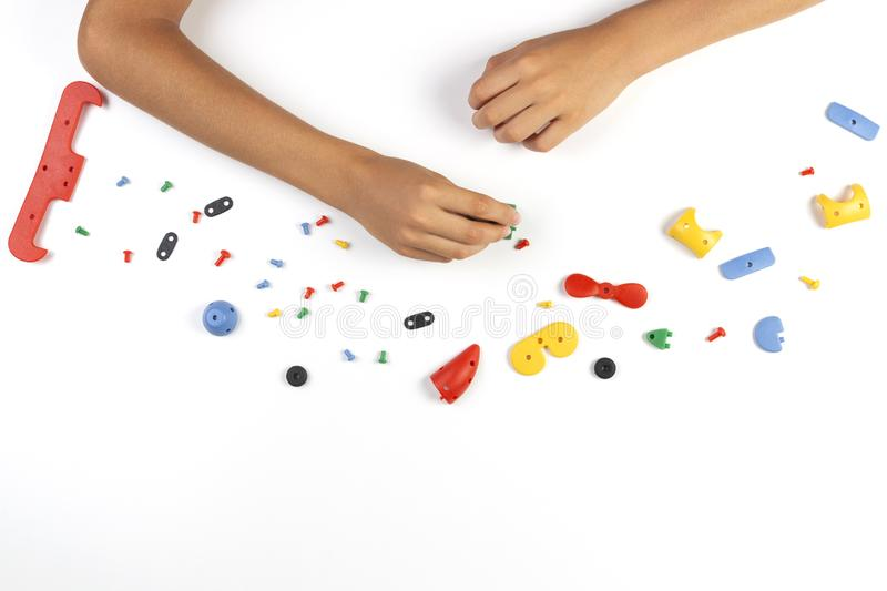 Kid hands playing with colorful plastic parts of constructor on white table. Top view stock photo