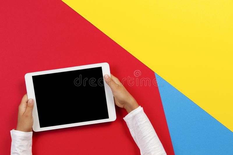 Kid hands with tablet computer on red, yellow and blue background stock photo