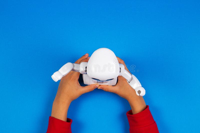 Kid hands with toy robot on blue background. stock images