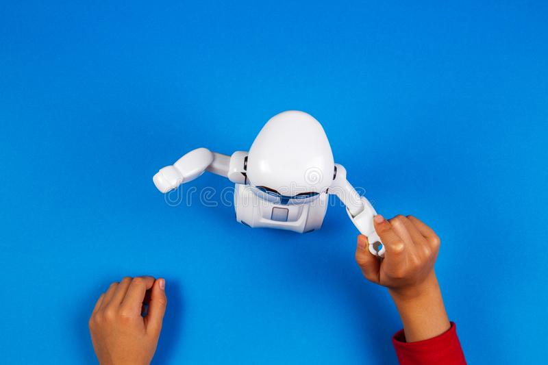 Kid hands with toy robot on blue background. royalty free stock photos