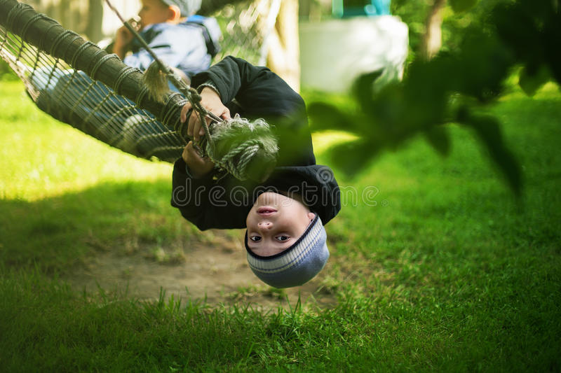 Kid hanging hammock upside down backyard background. Selective focus royalty free stock image