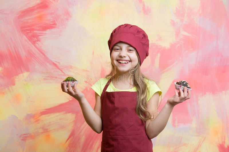 Kid, happy girl cook in red chef hat, apron. Cooking. kid or happy little girl cook in red chef hat and apron eating cupcake on colorful abstract background stock photos
