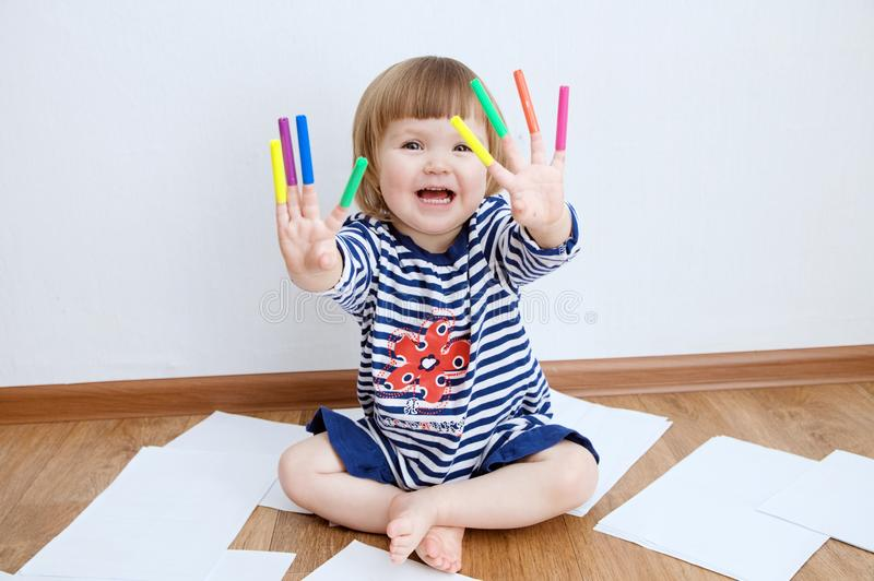 Kid happy smiling sitting on floor playing with felt tip pens. baby girl painting and playing. colorful stuff felt pen caps. On fingers of kid royalty free stock images