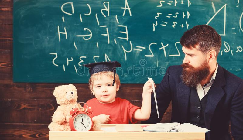 Kid happy studies individually with father, at home. Individual schooling concept. Teacher and pupil in mortarboard stock photography