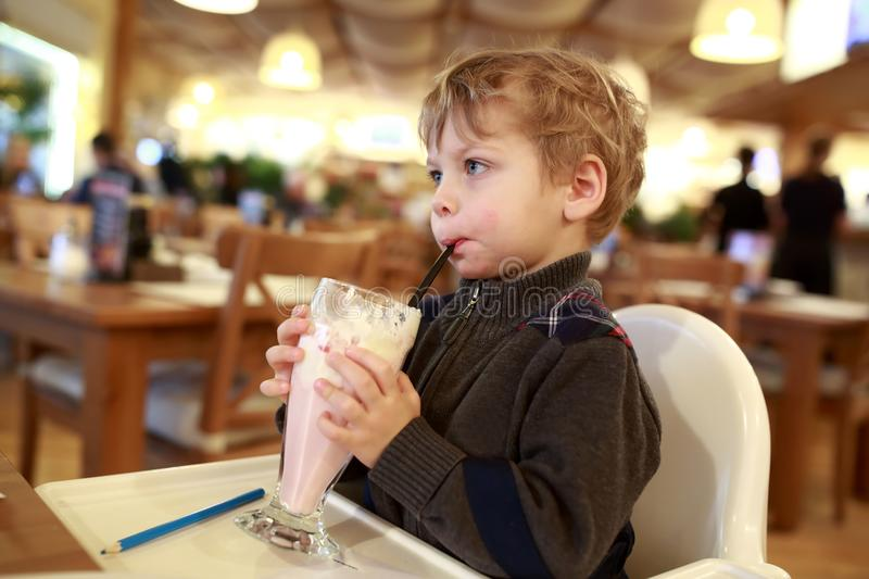 Kid has milkshake. At table in cafe royalty free stock photography