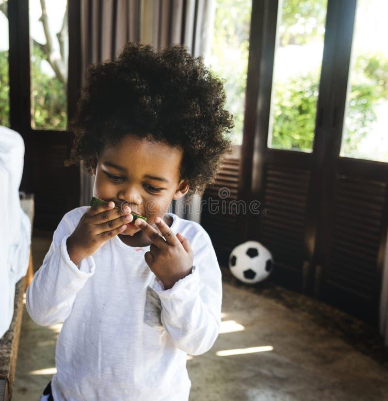 Kid having fun eating watermelon royalty free stock image