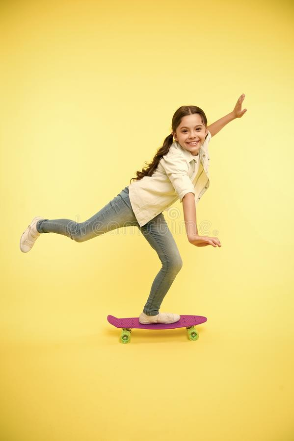 Kid having fun with penny board. Hobby favorite activity. Child smiling face stand on skateboard. Penny board cute. Colorful skateboard for girls. Lets ride stock image