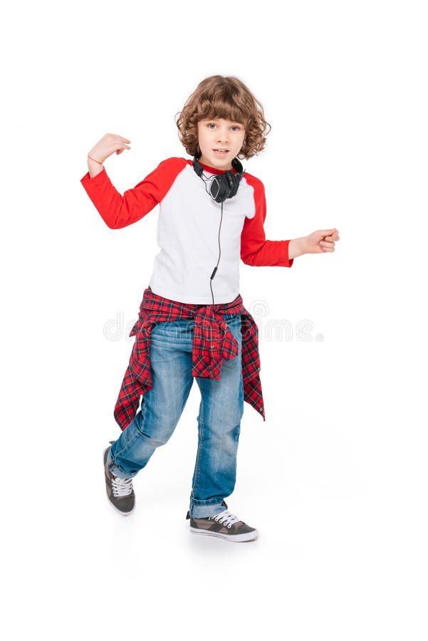 Kid with headphone dancing. Cute boy in headphone dancing isolated in white stock image