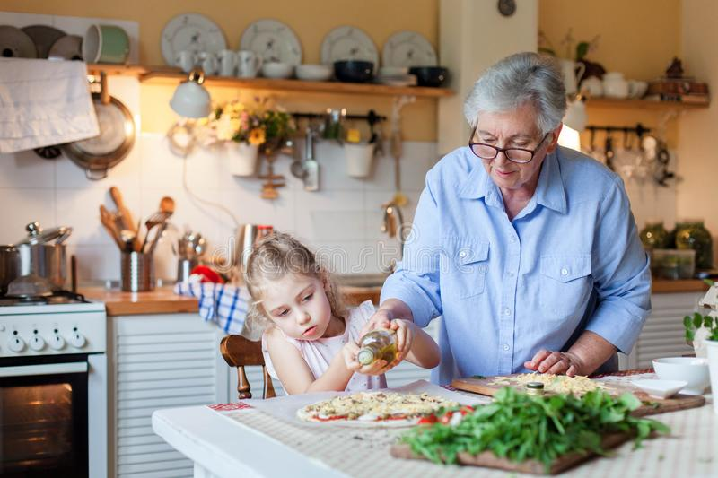 Kid is helping grandmother to cook italian pizza in cozy home kitchen for family dinner. stock photography