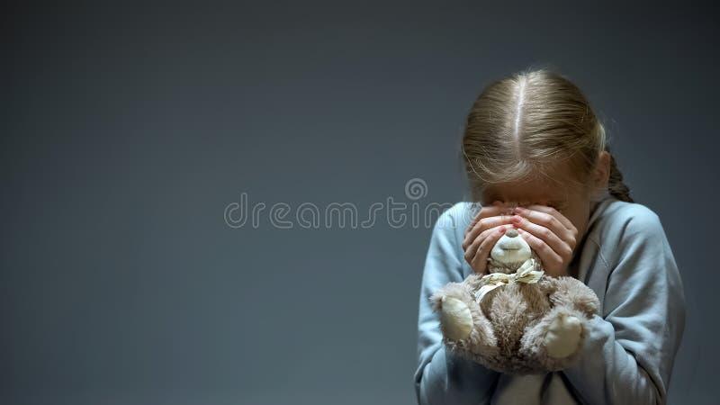 Kid hiding behind teddy bear, childish phobia and fear, family violence victim royalty free stock photo