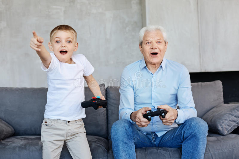 Kid and his grandpa playing video games together stock photos