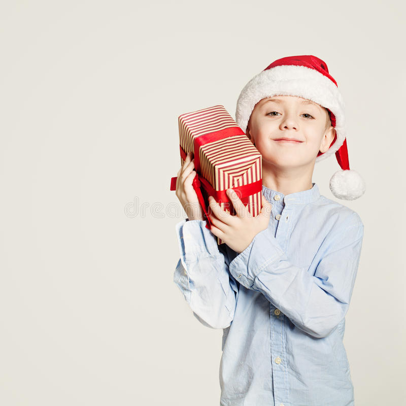 Kid holding Christmas Gift Box. Child Boy and Gift. On Background with Copy Space royalty free stock photos