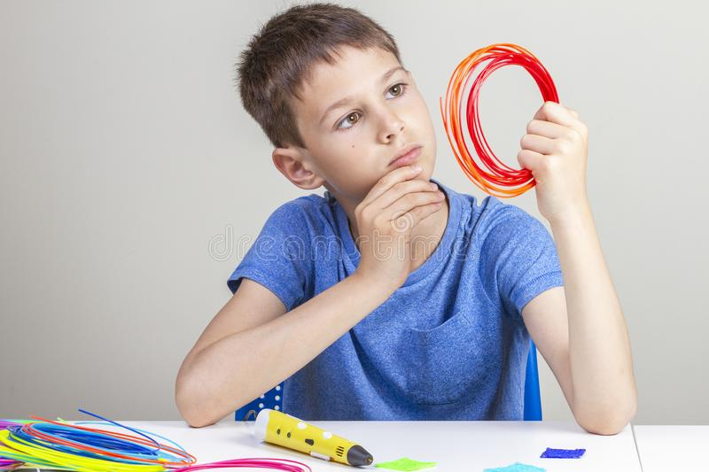 Kid holding 3d pen and colorful filaments for 3 d pen and thinking what to create royalty free stock images