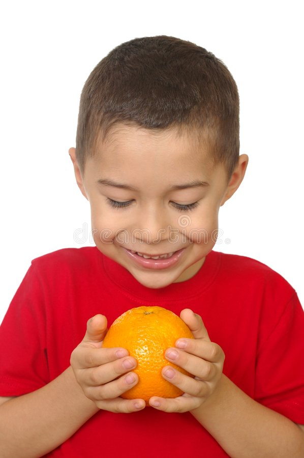 Kid holding an orange. Seven year old hispanic boy smiling and looking down at an orange in his hands, isolated on white background stock image