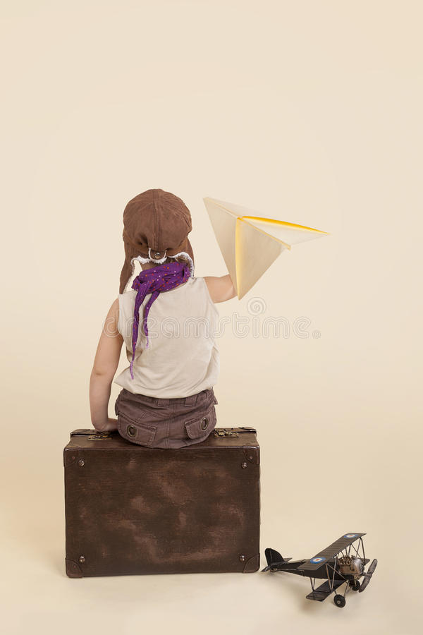 Kid holding paper airplane. stock photo