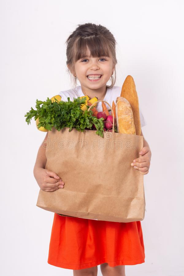 Kid holding paper grocery bag full of vegetables milk, bread. Happy child with grocery bag full of healthy food isolated on white. royalty free stock photo