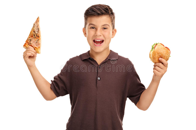 Kid holding a sandwich and a slice of pizza stock image