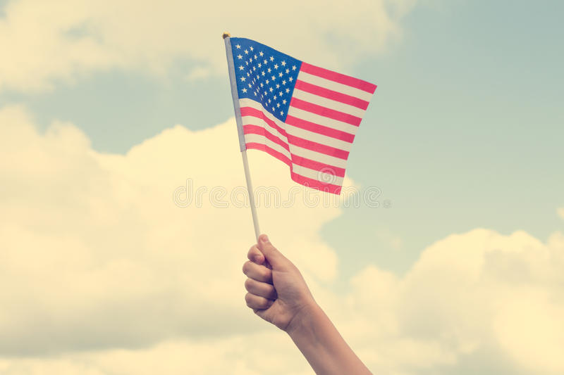 Kid holding small US flag. Child holding small US flag on the sky background royalty free stock photos