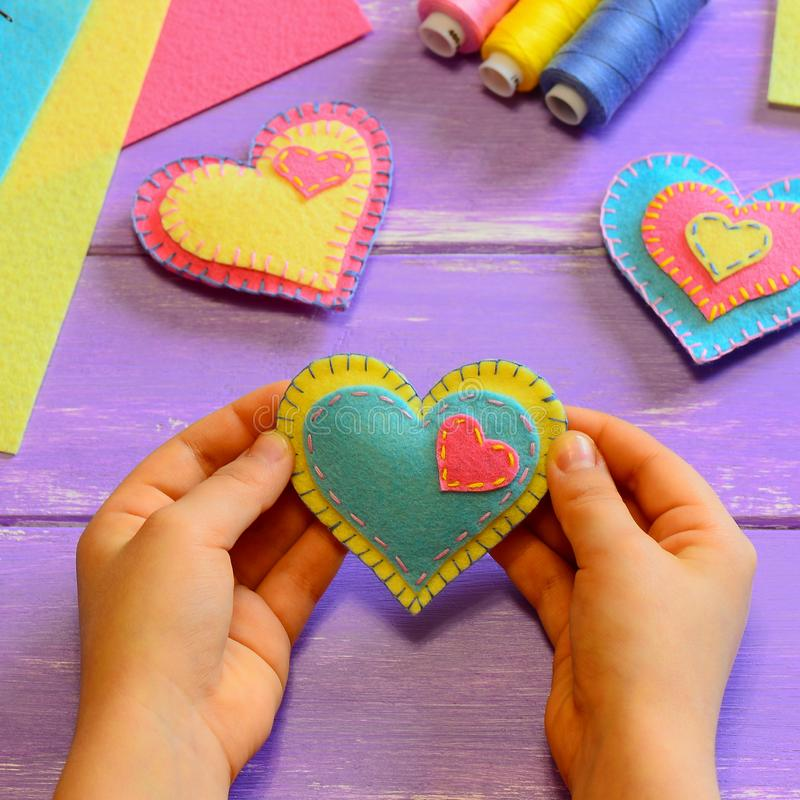 Kid holds a felt heart in his hands. Kid show a felt heart. Hearts decor, scissors, thread, felt sheets on a wooden table stock photos