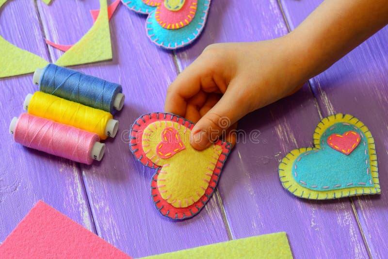 Kid holds a felt heart valentine in his hand. Kid made a felt heart valentine. Colorful felt hearts, scissors, thread set royalty free stock photos