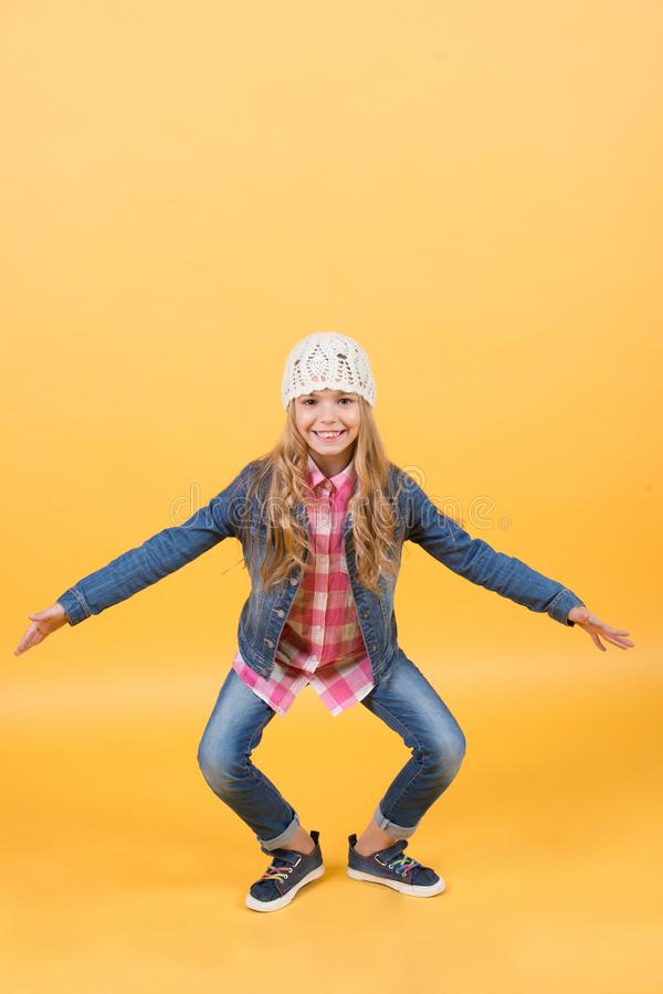 Kid in jeans suit, hat, plaid shirt crouch smiling. On orange background. Happy childhood and child. Girl fashion, style, trend concept royalty free stock images