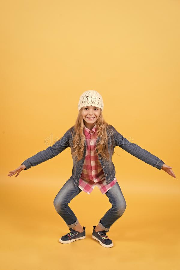 Kid in jeans suit, hat, plaid shirt crouch smiling. On orange background. Happy childhood and child. Girl fashion, style, trend concept stock photography