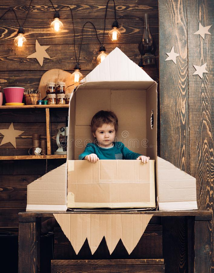 Kid with jet pack. Child playing at home. Success, leader and winner concept. little boy in paper rocket. stock photography
