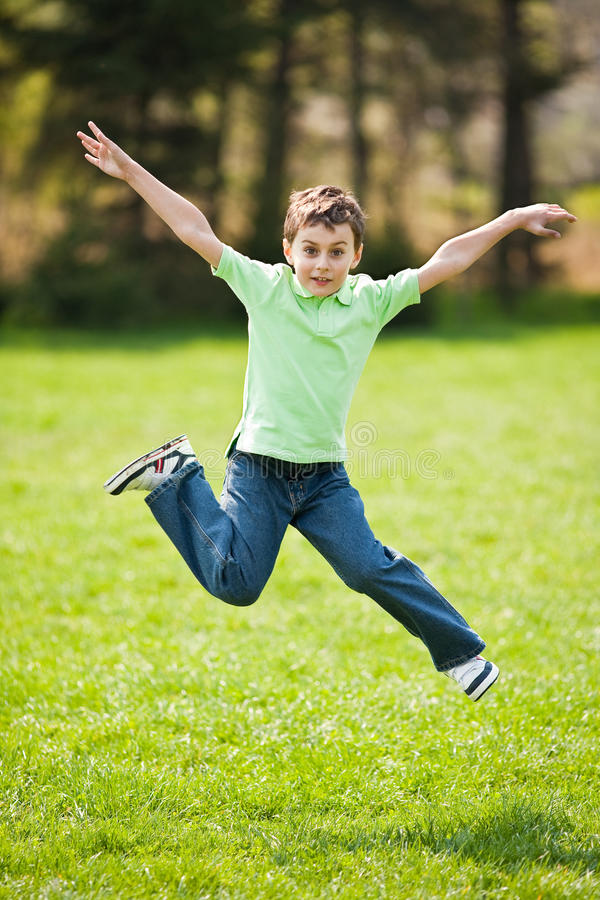 Kid Jumping For Joy Stock Photo
