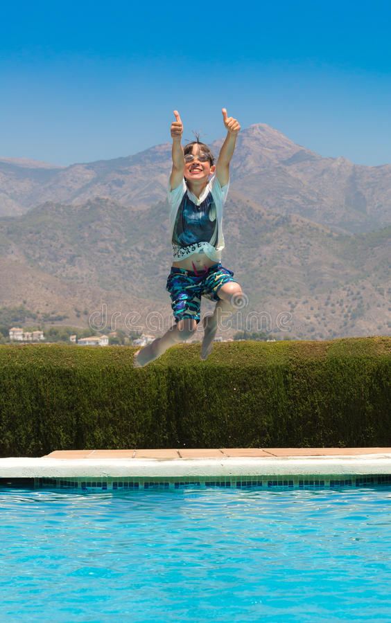 Kid jumping into pool stock photography