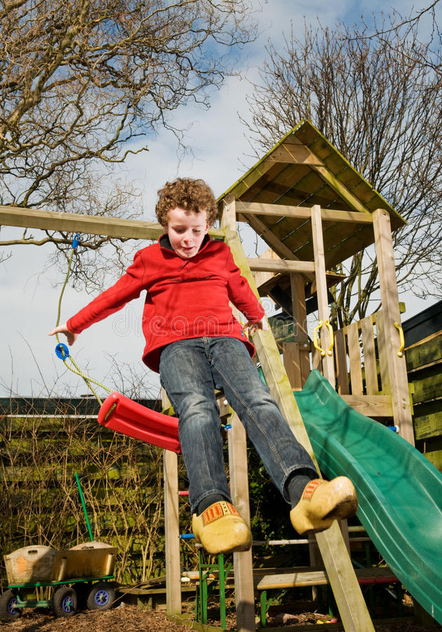 Kid jumping from swing stock images