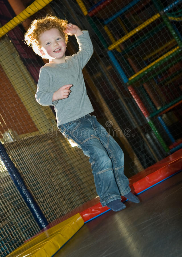 Kid jumping on trampoline royalty free stock photography