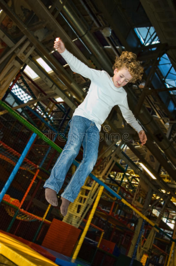 Kid jumping on trampoline royalty free stock photos