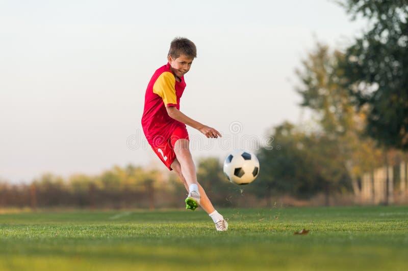 Kid kicking a soccer ball stock photography