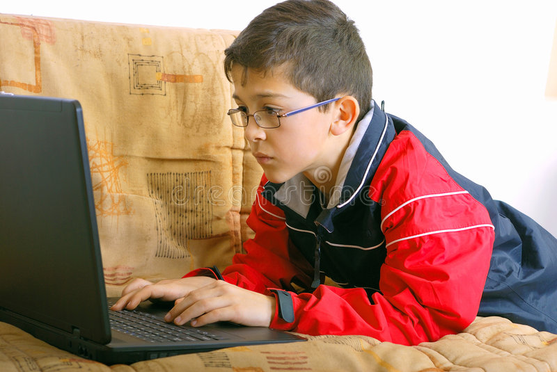 Kid and laptop. Kid playing computer games on the laptop in living room stock photo