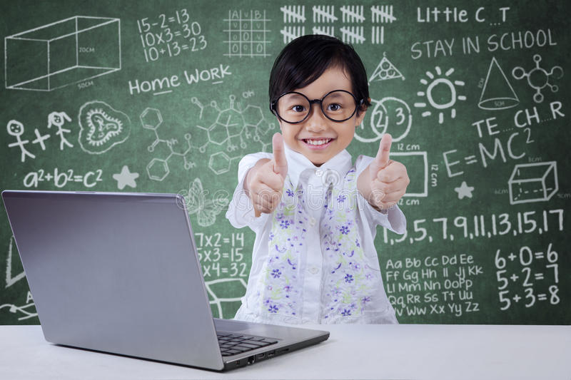 Kid with laptop shows OK sign. Lovely little girl with laptop on desk and showing thumbs up in the classroom with scribble background on the blackboard royalty free stock image