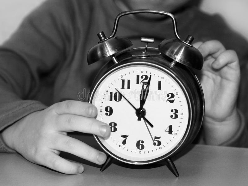 Kid with a large alarm clock royalty free stock photo