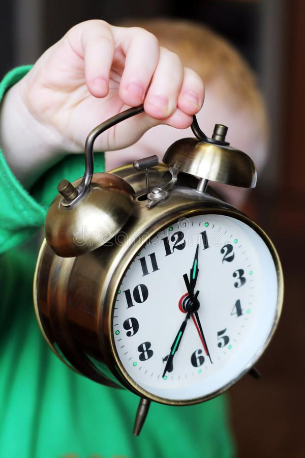 Kid with a large alarm clock royalty free stock image