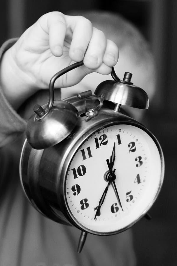 Kid with a large alarm clock stock photos