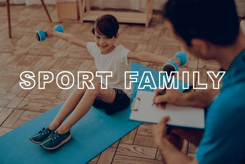 Kid Is Laying On Gym Carpet. Dumpbells Exercises. Active Holiday. Sports Clothes. Getting Better. Working Out At Home. Training Day. Repeating Practice. Body royalty free stock photos