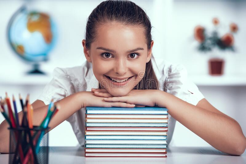 Kid is Leaned to Books Stack at Primary School. royalty free stock photo